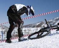 De fietser van de sneeuw in de winterbergen, ongeval stock afbeelding