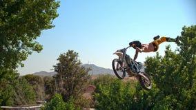 De fietser van de vrij slagmotocross voert de truc in sprong bij fmxcompetities uit stock afbeelding