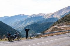 De fietsermens kijkt aan afstand Avonturenmotorfiets en berg, enduro, van weg, mooie mening, gevaarsweg in bergen, vrijheid royalty-vrije stock foto