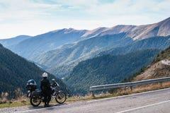 De fietsermens kijkt aan afstand Avonturenmotorfiets en berg, enduro, van weg, mooie mening, gevaarsweg in bergen, vrijheid royalty-vrije stock fotografie