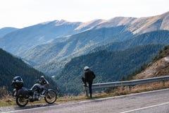 De fietsermens kijkt aan afstand Avonturenmotorfiets en berg, enduro, van weg, mooie mening, gevaarsweg in bergen, vrijheid stock foto