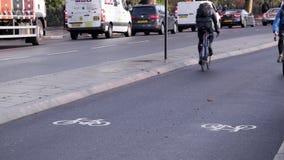De fietsers berijden in een bezige cyclussteeg in Londen met naast verkeer stock video
