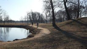 De fietsers doen sporten en gaan op een verlaten streek van het wegpark stock video