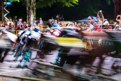 De fietsers slepen rond Hoek mee bij Schemering Stock Afbeeldingen