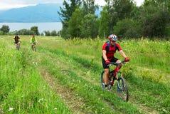 De fietsers van de berg op weg naast meer Stock Foto's