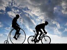 De fietsers van het silhouet op fietsen Stock Afbeelding