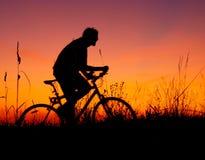 De fietsersilhouet van de berg in zonsondergang Royalty-vrije Stock Afbeelding