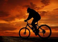 De fietsersilhouet van de berg in zonsopgang Stock Afbeelding