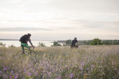 De fietsruiters berijden in openlucht op de gebieden dichtbij meer stock afbeelding