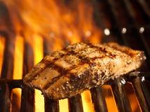 De filet van de zalm op de grill met vlammen Stock Foto