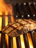 De filet van de zalm op de grill met vlammen royalty-vrije stock afbeelding