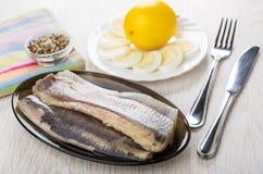 De filet van haringen, citroen, kookte eieren, specerij, mes en vork royalty-vrije stock afbeelding