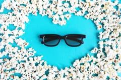De film, het tijdverdrijf, het vermaak en de bioskoop van de conceptenliefde Popcornvorm van hart en 3d glazen op blauwe achtergr stock foto