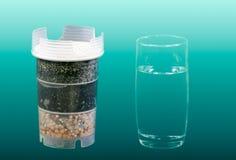 De filter van de waterreiniging en een glas schoon drinkbaar water stock afbeeldingen