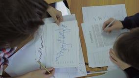 De financiële adviseurs bekijken grafiek en document aan stock video