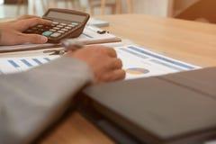 de financiële calculator van het adviseursgebruik om opbrengst & begroting te berekenen stock afbeelding