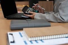 de financiële calculator van het adviseursgebruik om opbrengst & begroting te berekenen stock afbeeldingen