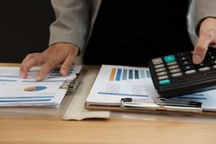 de financiële calculator van het adviseursgebruik om opbrengst & begroting te berekenen stock foto