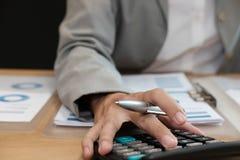 de financiële calculator van het adviseursgebruik om opbrengst & begroting te berekenen stock fotografie