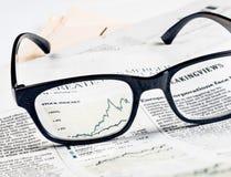 De financiële grafiek en de grafiek van voorraadindexen zien door glazenlens op financiële krant Stock Afbeeldingen