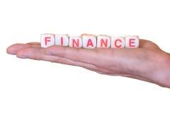 De financiën die met houten worden geschreven dobbelen op een hand, die op witte achtergrond wordt geïsoleerd Stock Afbeeldingen