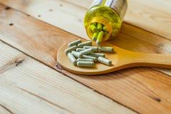 De fines herbes dans la capsule sur la table en bois Photo stock