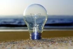 De firma van Lightbulbtribunes op het strand met water op de achtergrond stock fotografie