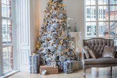 De flat is verfraaid met een Kerstboom, onder de boom zijn giften Stock Foto