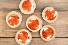 De flera tartletsna med den röda kaviaren och smör på träbrun bästa sikt för tabell Arkivbild