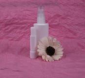 De fles en de bloem van de schoonheidsmiddelenuitrusting op roze achtergrond Stock Foto