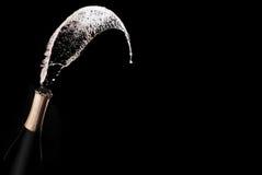 De fles en de nevel van Champagne op zwarte backgroun stock fotografie