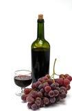De fles en het wijnglas van de wijn met druif Stock Afbeeldingen