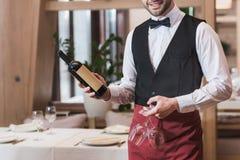 De fles en de wijnglazen van de kelnersholding Royalty-vrije Stock Fotografie