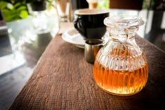 De fles honing met koffie plaatste na dient aan de klant Stock Afbeeldingen