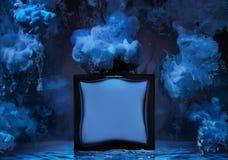 De fles mensen` s parfum in een watergolf met clubs van blauwe verf rond de fles Stock Fotografie
