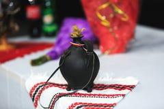 De fles of plosca confectioned in zwarte gebakken klei De riem van het leer stock fotografie