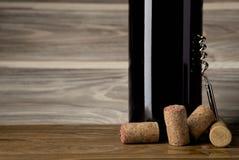 De fles rode wijn met een kurketrekker en kurkt Op een houten lijst royalty-vrije stock afbeelding