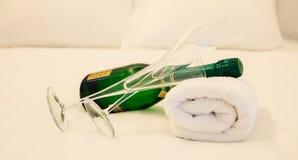 De fles van Champagne ` s en paar die van glazen op witte handdoek leggen Witte beddegoedachtergrond, close-upmening stock afbeeldingen