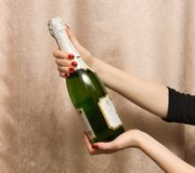 De fles van de holding met champagne Stock Afbeeldingen