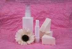 De fles van de schoonheidsmiddelenuitrusting met spons en bloem op roze achtergrond stock fotografie