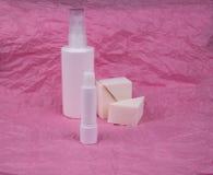 De fles van de schoonheidsmiddelenuitrusting met spons op roze achtergrond royalty-vrije stock foto