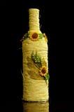 De fles van de wijn die in gele kabel wordt verpakt Stock Foto