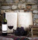 De fles van de wijn en oude boeken Stock Afbeelding