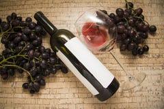 De fles van de wijn met glas en druiven Stock Foto