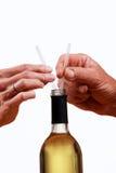 De fles van de wijn met handen die twee stro houden. Stock Foto's