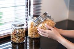 De fles van de handgreep van macaroni in keuken royalty-vrije stock afbeeldingen