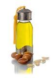 De fles van het glas argan olie met noten en zaden stock afbeelding