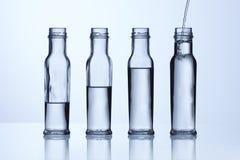 De fles van het glas met verschillende waterspiegels Royalty-vrije Stock Afbeeldingen