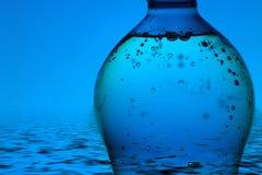 De fles van het mineraalwater op blauwe achtergrond royalty-vrije stock foto's