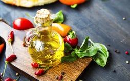 De fles van het olijfolieglas met kruiden en basilicumkruid Stock Afbeelding